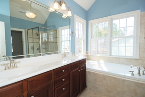 A view of a master bathroom vanity and tub set up.