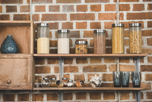 Jars of dry food on shelves mounted to brick wall