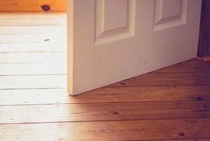 White door swinging open across a wood floor