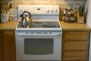 A white electric stove with a kettle on the burner.