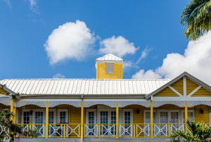 A tin roof on a yellow home.
