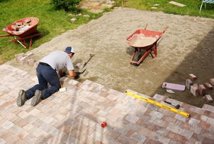 Person installing large area of pavers