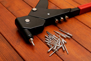 a rivet gun with rivets laying next to it