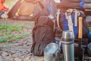camping backpack with cooking gear on camp site