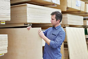A man shopping for plywood in a home improvement store.