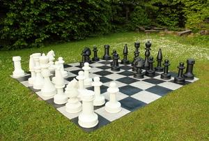 A life-sized backyard chess board in a backyard.