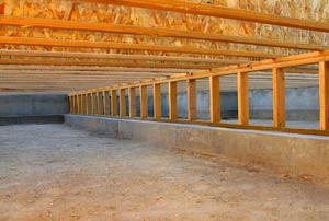 Looking down the length of an unfinished crawl space.