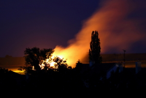 A fire at dusk in a neighborhood.