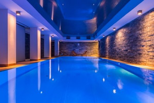 Indoor pool with side lighting on stone walls