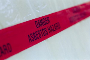 A red tape sign warning against asbestos danger.