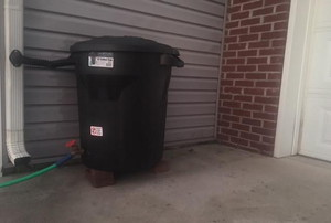 A rain barrel outside a garage.