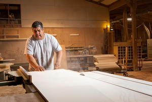 Man cutting a large sheet of plywood on a table saw