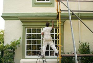 A professional painter working on a home exterior.