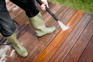 Using a power washer to clean a wood deck.