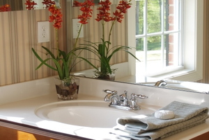 A bathroom prepped for guests with fresh hand towels and flowers.