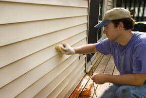 A man cleans siding.