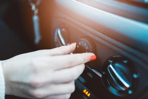 A female hand adjusting the vent on a car dashboard.