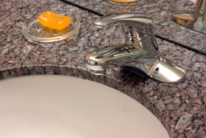 A Corian bathroom countertop, soap, and faucet.