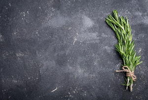 A concrete counter with a sprig of herbs on it.