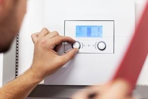 Man adjusting dial on a boiler