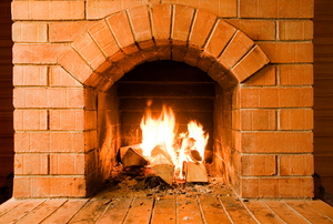 A brick masonry fireplace with a lit fire.