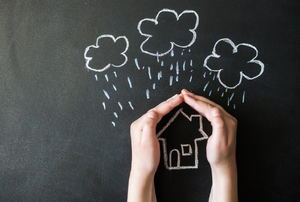 A chalkboard drawing of a house under rain clouds with hands protecting the house.