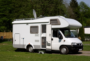 White RV parked with door open and dish on top