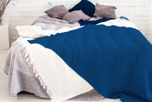 a bed piled up with grey and blue pillows and a blue comforter