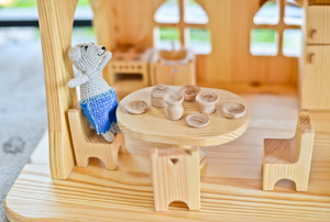 A wooden dollhouse with a tiny table