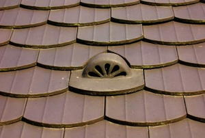 A stylized attic vent surround by matching, brown roofing tiles.