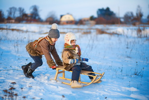 Two kids playing on a sled in the snow.