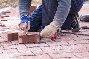 someone kneeling down next to two bricks