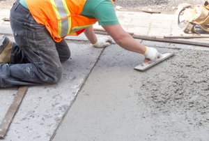 a person spreading concrete