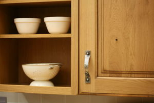 a kitchen cabinet with dishes on a shelf next to it