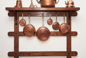 Copper utensils hanging on a rack.