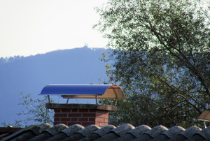 A chimney against the skyline with a tree and mountains.