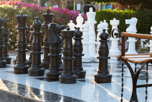 large scale chess set on patio near bench and bushes