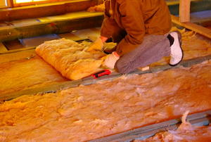 A worker adding batt insulation to a floor.