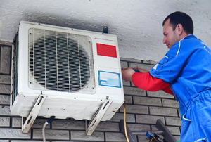A man does air conditioner maintenance.