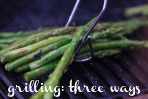 """A bunch of asparagus on an electric grill with tongs picking them up and the words """"grilling: three ways."""""""