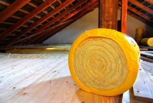 A roll of insulation waiting to be installed on the floor of an attic.