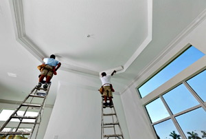 Two men on ladders installing molding around the edges of a tray ceiling.