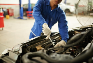 a person in blue working on a car
