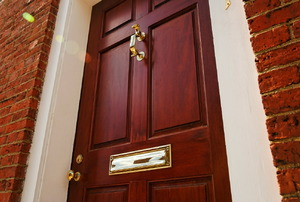 burgundy front door with brass hardware
