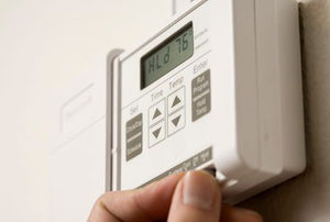 A homeowner adjusting the settings on a digital thermostat.
