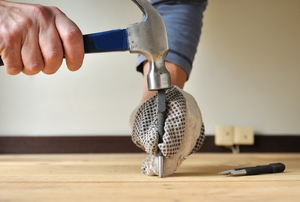 A hammer and nail set punching a nail into a wood floor.