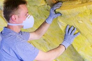 a man installs a sheet of insulation