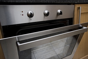 A built-in oven with the door ajar.