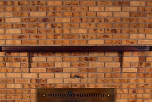 A wooden mantel on a brick fireplace.