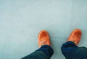 A pair of brown men's shoes on a blue tile floor.